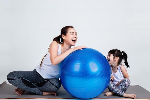 Potomstwo matka z małym córki ćwiczeniem na sprawności fizycznej piłce