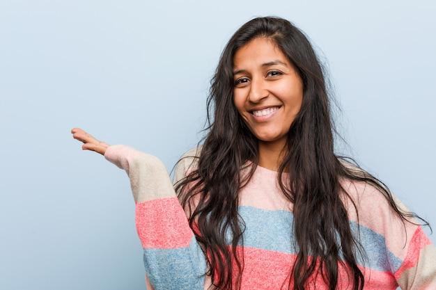 Potomstwo mody indyjska kobieta pokazuje odbitkową przestrzeń na palmie i trzyma inną rękę na talii.