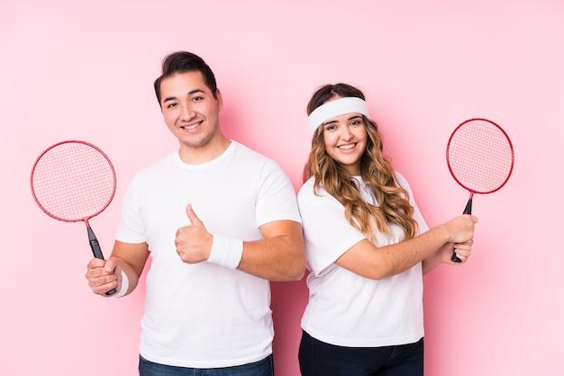 Potomstwo para bawić się badminton odizolowywał uśmiecha się kciuk up i podnosi