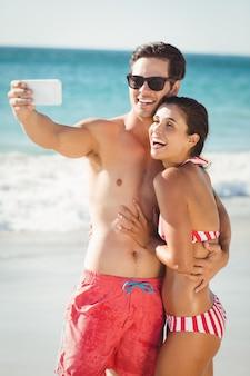 Potomstwo para bierze selfie na plaży
