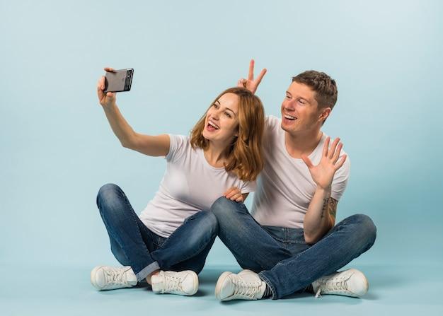 Potomstwo para bierze selfie na telefonie komórkowym przeciw błękitnemu tłu