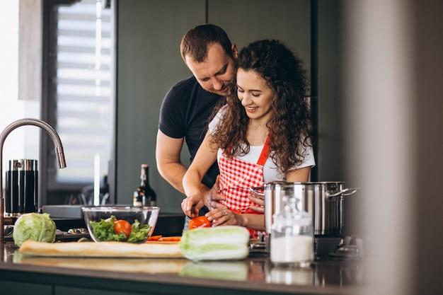 Potomstwo para gotuje wpólnie przy kuchnią