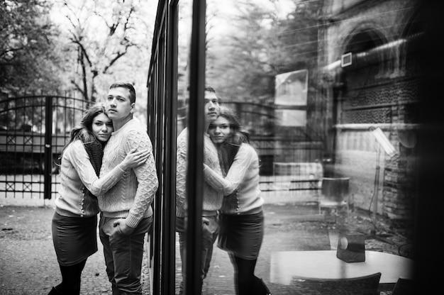 Potomstwo para jest ubranym na wiązanych ciepłych pulowerach ściska w miłości tle odzwierciedla odbicie na okno.