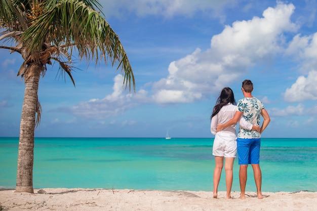 Potomstwo para na biel plaży podczas wakacje. szczęśliwa rodzina spędza miesiąc miodowy