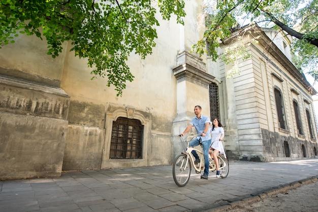 Potomstwo para na retro tandemowym bicyklu przy ulicznym miastem