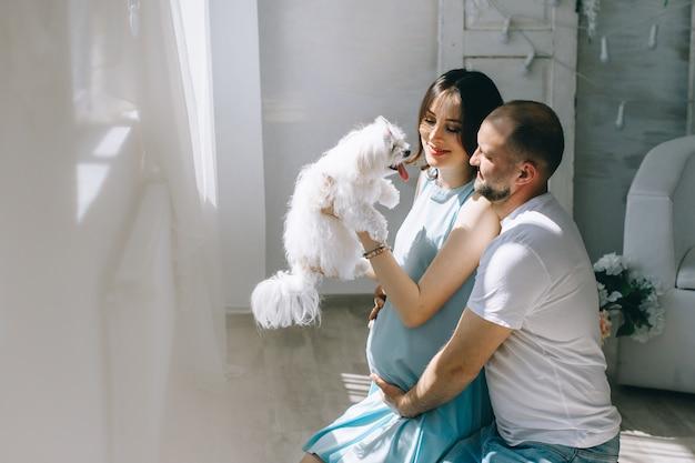 Potomstwo para oczekuje dziecka stoi wpólnie indoors