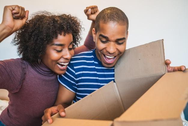 Potomstwo para otwiera pakunek w domu.