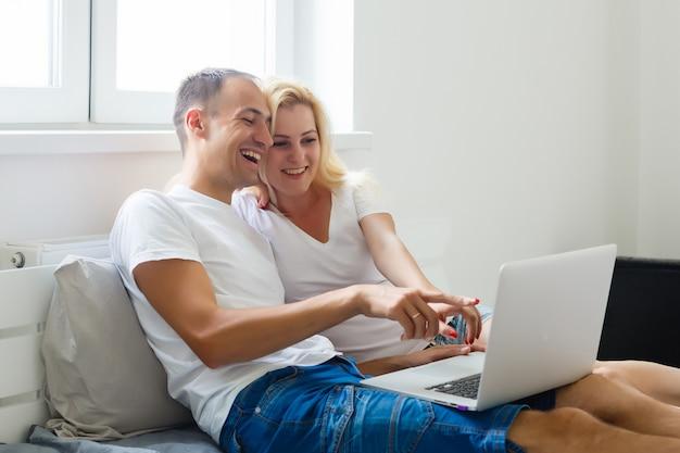Potomstwo para relaksuje w łóżku. szczęśliwi czule potomstwa dobierają się relaksować w łóżku bawić się one śmia się w rozrywce z ich laptopem. interracial couple, asian woman, caucasian man…