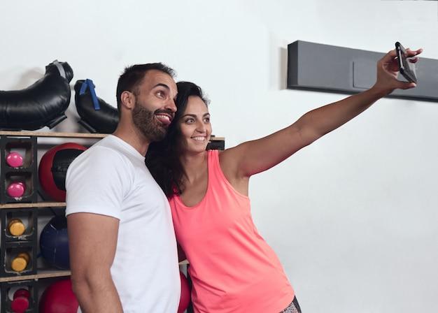 Potomstwo para robi selfie przy gym. uśmiecha się, gdy wyciąga język, robiąc miny.