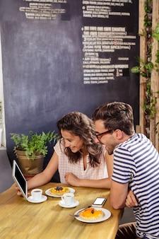 Potomstwo para używa cyfrową pastylkę w bufecie