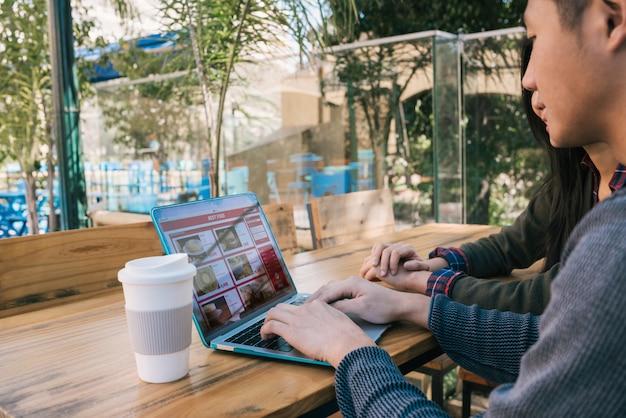 Potomstwo para używa laptop przy sklep z kawą.