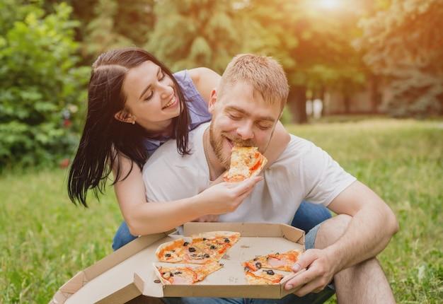 Potomstwo pary łasowania pizza w parku. traktują się i śmieją.