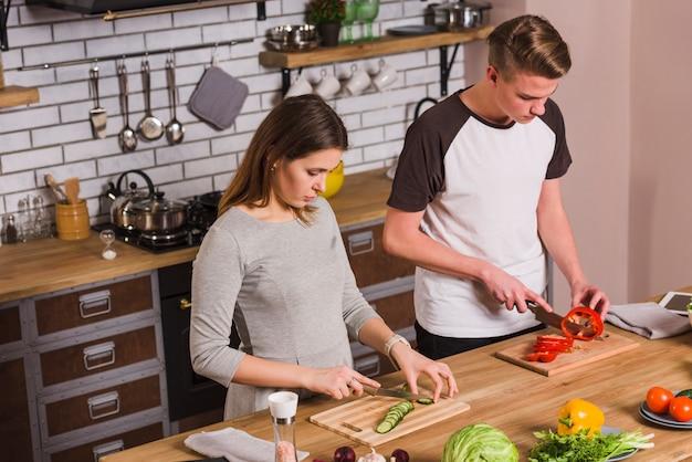 Potomstwo pary tnący warzywa w kuchni