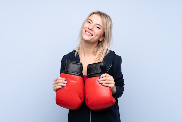 Potomstwo sporta blondynki kobieta nad odosobnioną błękit ścianą z bokserskimi rękawiczkami