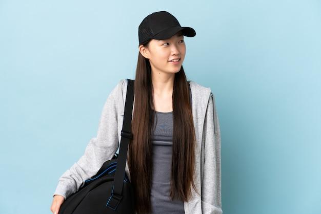 Potomstwo sporta chińska kobieta z sport torbą nad odosobnionym błękitnym główkowaniem pomysł podczas gdy przyglądający up