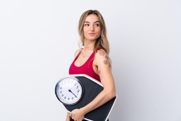 Potomstwo sporta kobieta nad odosobnioną biel ścianą z ważyć maszynę