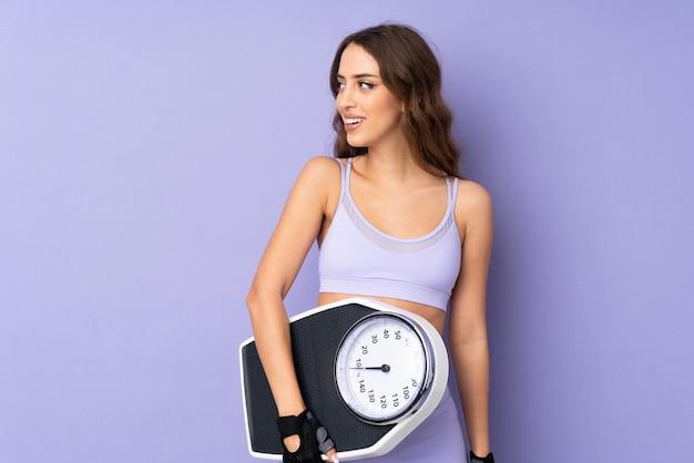 Potomstwo sporta kobieta nad odosobnioną purpury ścianą z ważyć maszynę