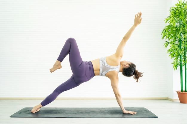 Potomstwo sporta kobiety ćwiczenie z joga w domu