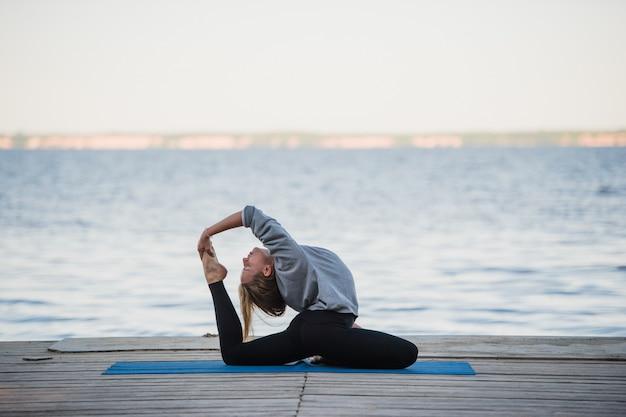 Potomstwo sporta kobiety ćwiczy joga na plaży