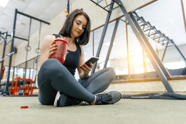 Potomstwo sportów kobieta odpoczywa na podłoga po ćwiczeń w gym