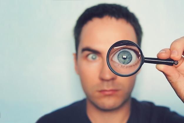 Potrait młody człowiek patrząc przez szkło powiększające na białym tle niewyraźne. zobacz męskie niebieskie oko przez obiektyw. lupa z okiem makro w ręce osoby na pierwszym planie. wyszukiwanie informacji.