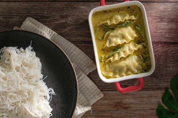 Potrawa fusion z zielonym curry z knedlami. zielone curry (kaeng kheiyw hwan) z tajskim jedzeniem