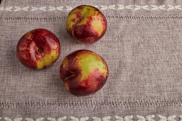 Potrójne czerwone jabłka na białym tle na stole w kuchni.