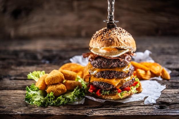 Potrójny burger wołowy z jajkiem i nuggetsami z sera w ciemnym drewnianym otoczeniu.
