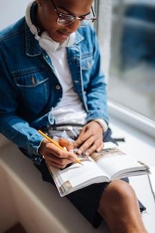 Potrzeba sprawdzenia. poważny ciemnoskóry student pochyla głowę, patrząc na swoją książkę