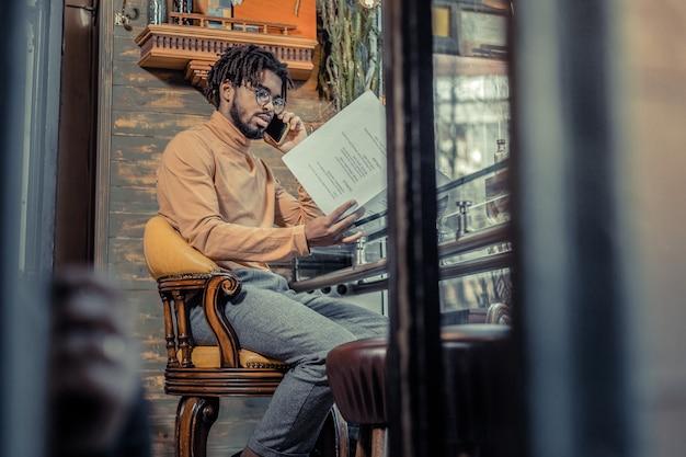 Potrzeba sprawdzenia. poważny mężczyzna siedzi w półpozycji podczas sprawdzania dokumentów