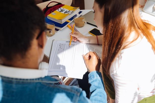 Potrzeba sprawdzenia. skoncentrowana długowłosa dziewczyna siedząca obok koleżanki i patrząca na tabelę odpowiedzi