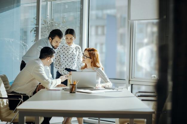 Potrzebna opinia. optymistyczni młodzi koledzy zgromadzeni wokół swojego szefa z laptopem i razem oglądający prezentację swojego nowego projektu