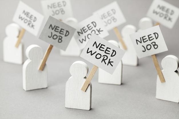 Potrzebna praca. tłum bezrobotnych z plakatami na szarym tle