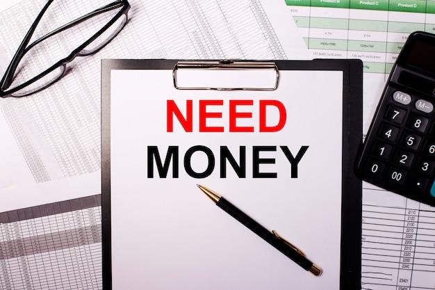 Potrzebne pieniądze jest zapisane na białej kartce papieru, obok okularów i kalkulatora.