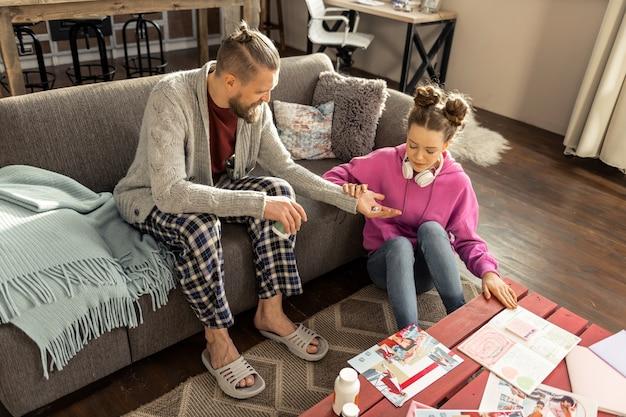 Potrzebne środki depresyjne. ojciec w kanciastych spodniach, podający swojej zestresowanej córce środki uspokajające