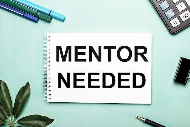 Potrzebny mentor jest napisany na białej kartce na niebieskim tle w pobliżu papeterii i arkusza schefflera. wezwanie do działania. motywacyjna koncepcja