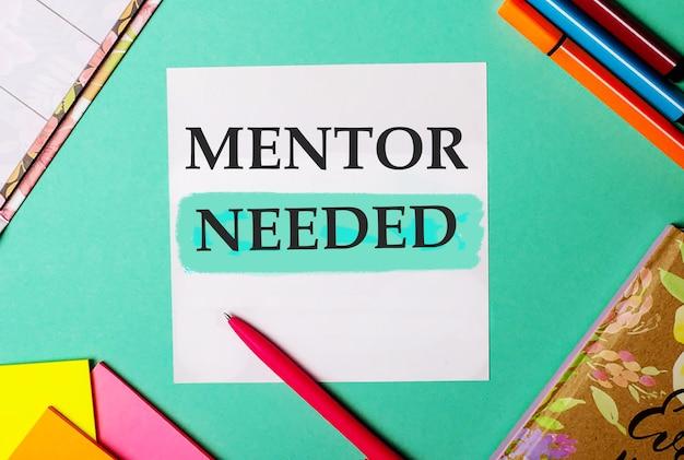 Potrzebny mentor napisany na turkusowym tle w pobliżu jasnych naklejek, notesów i markerów