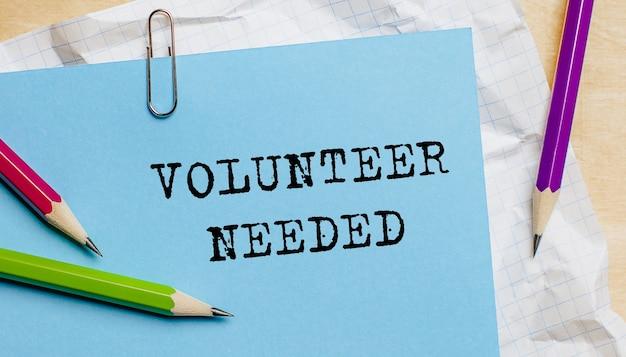 Potrzebny wolontariusz tekst napisany na papierze ołówkami w biurze