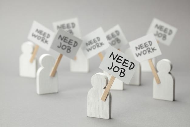 Potrzebować pracy. tłum bezrobotnych z plakatami na szarym tle