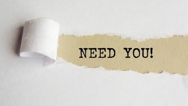 Potrzebuję cię. słowa. tekst na szarym papierze na tle rozdarty papier.