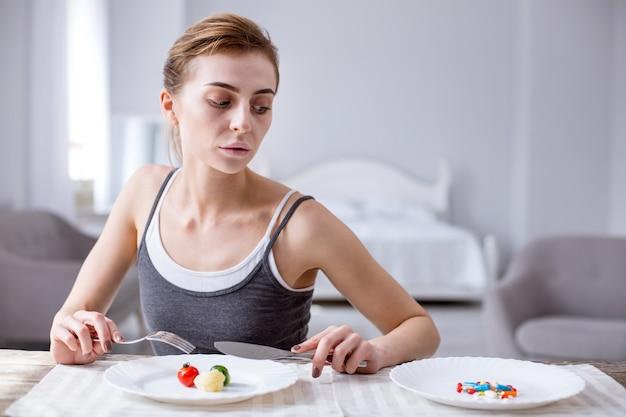 Potrzebuję lekarstwa. smutna przygnębiona kobieta siedzi przy stole, patrząc na tabletki talerza