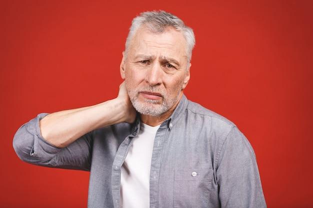 Potrzebuję masażu. sfrustowany starszy mężczyzna trzyma rękę na jego szyi w przypadkowej odzieży podczas gdy stojący.