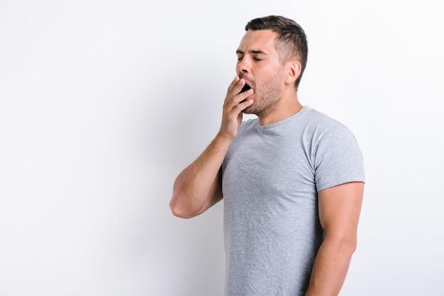Potrzebuję odpoczynku. portret senny brunetka mężczyzna z brodą w dorywczo biały t-shirt ziewanie i zakrywanie ust ręką, uczucie wyczerpania, brak snu. kryty studio strzał na białym tle