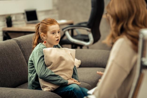 Potrzebuję pomocy. śliczna rudowłosa dziewczyna trzyma poduszkę podczas rozmowy ze swoim terapeutą podczas sesji