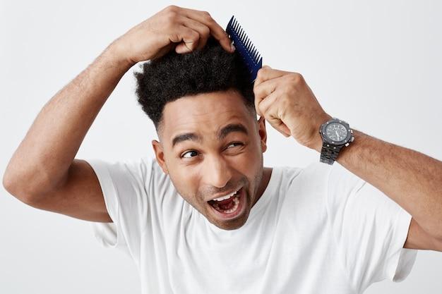 Potrzebujesz nowej fryzury. portret dojrzałego, zabawnego, pięknego, opalonego afrykańskiego faceta z kręconymi włosami w swobodnej białej koszulce mającej problemy z czesaniem włosów, wyglądającego na bok z bolesnym wyrazem twarzy