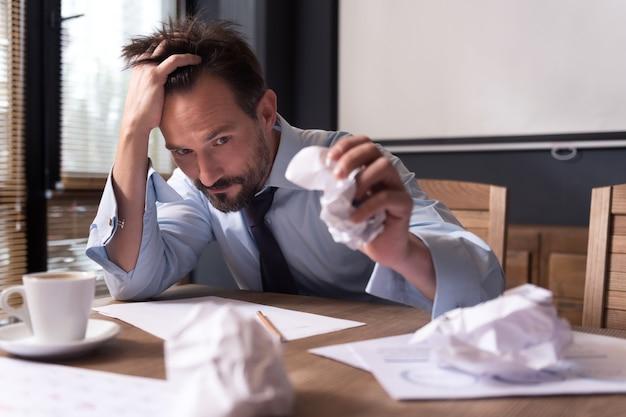 Potrzebujesz nowych pomysłów. wyczerpany, przygnębiony, przygnębiony mężczyzna trzymający się za głowę i zgniatający kartkę papieru, rozwiązując problem
