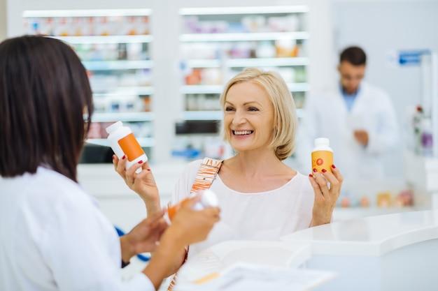 Potrzebujesz obu butelek. śliczna blondynka z uśmiechem na twarzy patrząc na swojego konsultanta