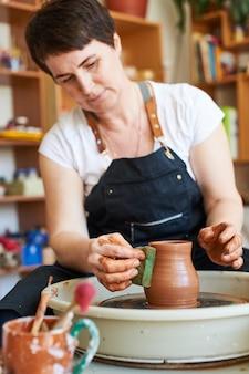 Potter kobieta pracuje na kole z wyrobem glinianym.