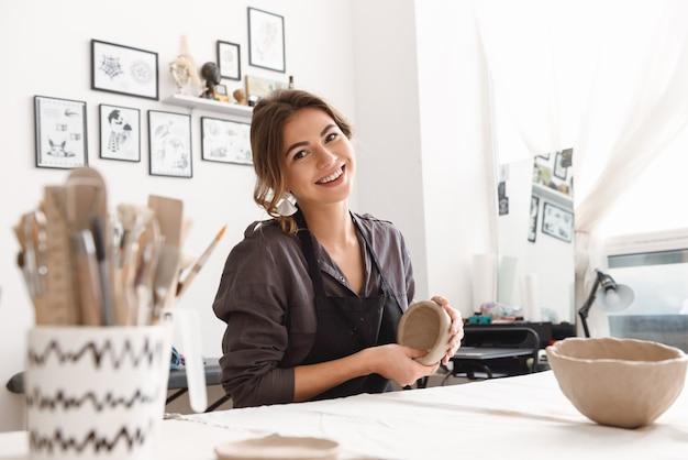 Potter młoda kobieta tworzenie potraw gliniany garnek