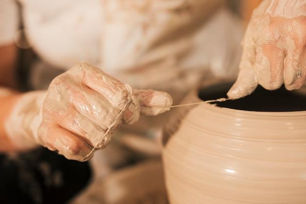 Potter przecina krawędzie ceramiki nicią na obracającym się kole
